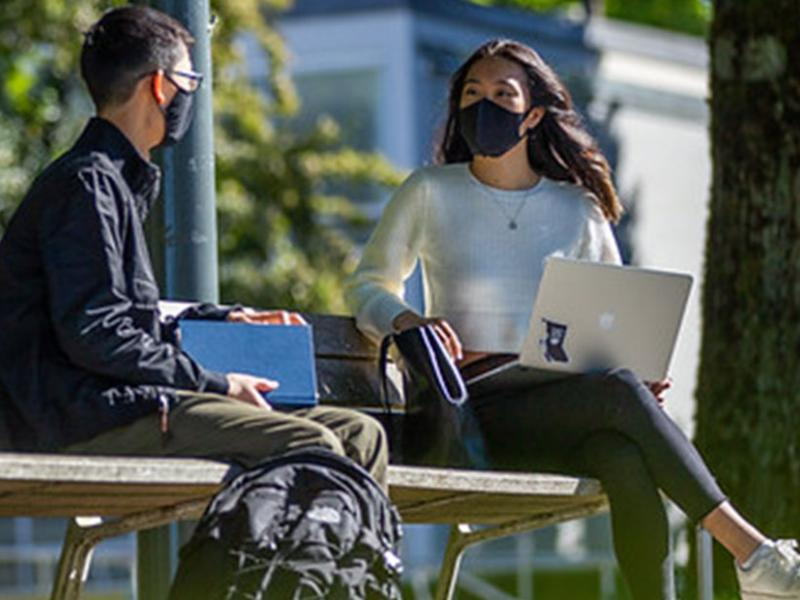 Two UBC students sitting on a bench wearing masks.