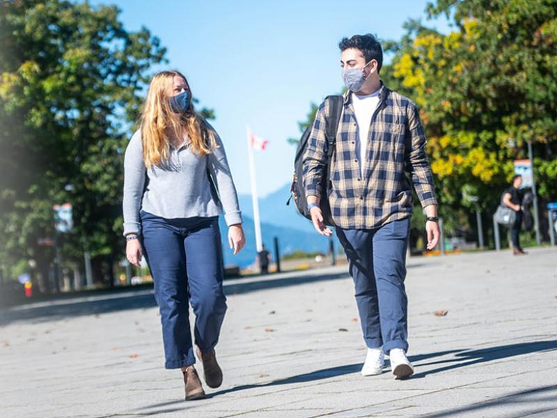 Two UBC students wearing masks walking down Main Mall