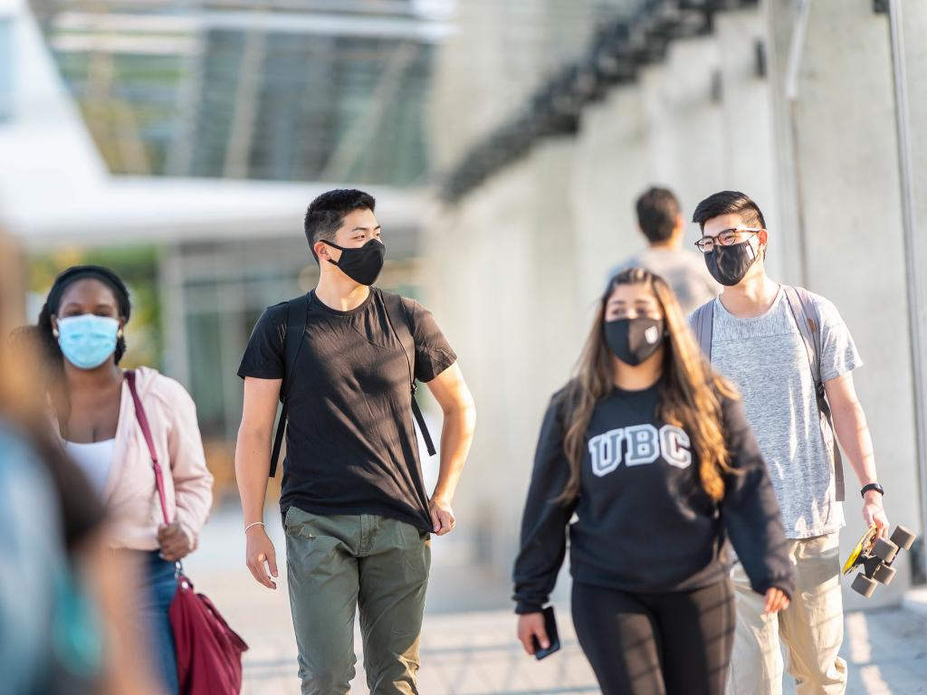 Group of socially distanced masked students walking on campus